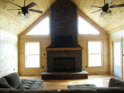 Greatroom with large rock fireplace, LCD TV, plenty of natural light, views