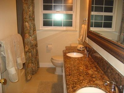 Beautiful guest bathroom with granite counters and double sink