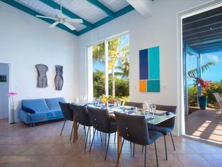 Providenciales - Provo villa photo - Ligne Roset dining area -10 foot sliding glass doors lead to mature exotic garde