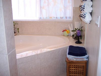 Master bath has designer tile, glass brick and a luxurious jacuzzi