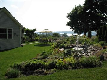 Manicured garden landscape with outdoor seating overlooking the harbor.