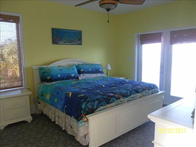 Yellow fish bedroom with king size bed, private bath and balcony.