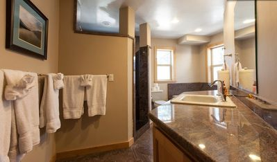 downstairs bath with walk-in shower, soaking tub, toilet and granite counters