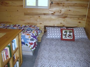 Upstairs bedroom with full and twin beds, plenty of adult and childrens' books