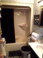 Rye condo photo - Bath with a tub, hairdryer, heat pad, linens & weight scale.