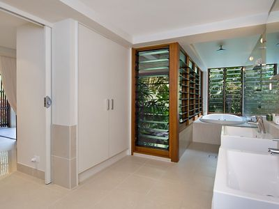 Bathroom 2, huge spa bath and shower overlooking vegetation