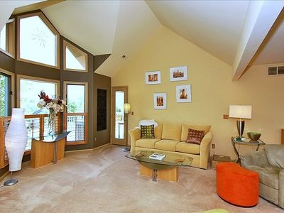 Vaulted ceiling and large picture windows in living room.