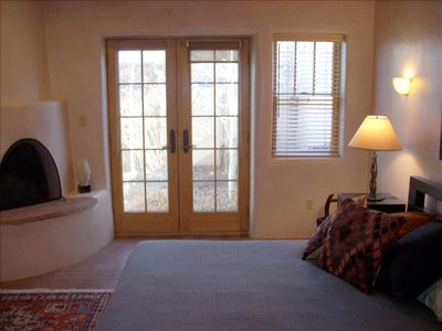 Master bedroom French doors to back courtyard, kiva wood burning fireplace