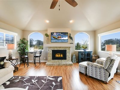 Living Room has comfortable sofa, big screen 3-D TV, fireplace and great views.