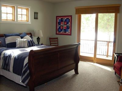 Master bedroom with double doors leading out to small deck facing golf course