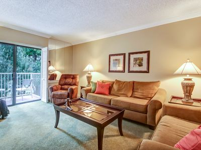 Comfy living room with view of balcony overlooking pool, golf course, and lake.