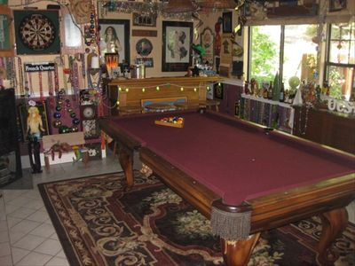 Game room pool table with darts, a bar and tons of art and memorabelia