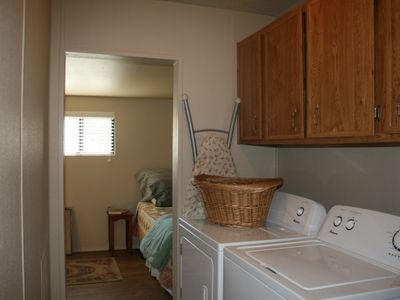 Laundry area equiped with a iron and ironing board