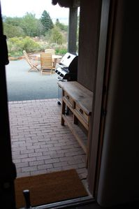 View from inside living room toward backyard. Gas grill and table under portal.