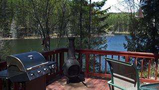 Columbia Falls cabin photo - Deck overlooking lake. Gas BBQ, chiminea, table & chairs.