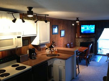 Snowshoe Mountain townhome rental - view of kitchen into dining room and living room with fireplace