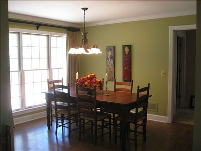 Dining room has lovely hardwood floors and seats 8