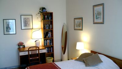 Bedroom showing desk, large floor mirror and paperback library