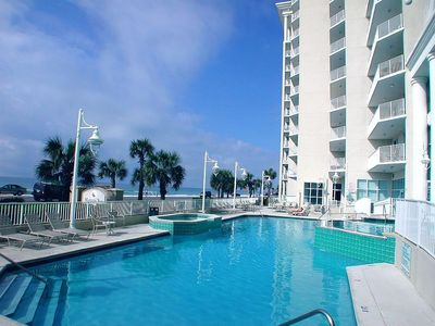 Outdoor pool and hot tubs have view of the Gulf