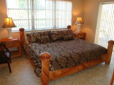 Master bedroom features king bed, new HDTV and opens to pool