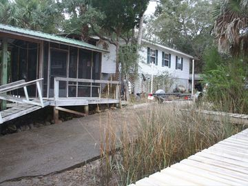 Concrete boat ramp, covered slip and screened boat house