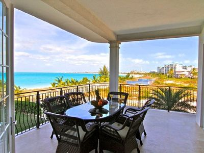 Outdoor dining overlooking Grace Bay to Leeward and North West Point, breeze