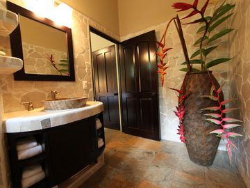 View of master bathroom entrance with rare pendant Heliconia flowers