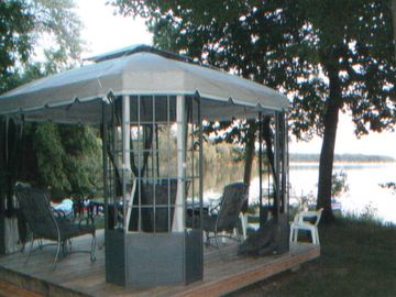 Dining table and five padded chairs in screened gazebo.
