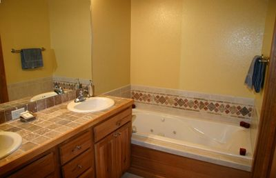 Master bathroom features 2 sinks, jacuzzi tub and tile shower