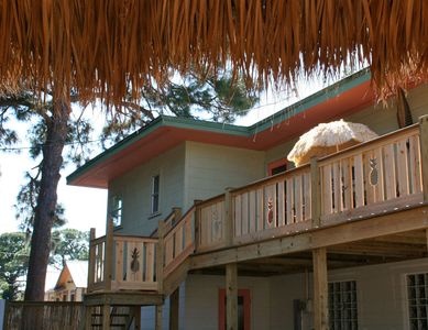 The balcony deck overlooks the yard, which has an all-weather tiki hut.
