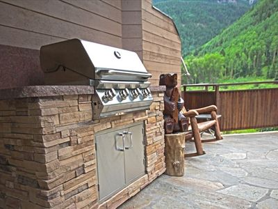 The deck features a built-in gas grill and outdoor furniture.