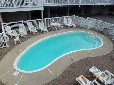 Boardwalk condo rental - Heated pool with chaises, tables and chairs