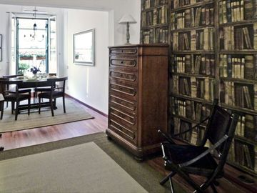 Entry area with leather chair, bureau, faux bookshelves is a little retreat