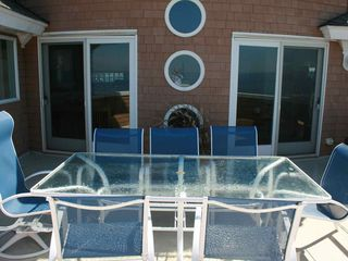 Upstairs patio, doors enter into living room, dining room, kitchen, bay behind - Holgate house vacation rental photo