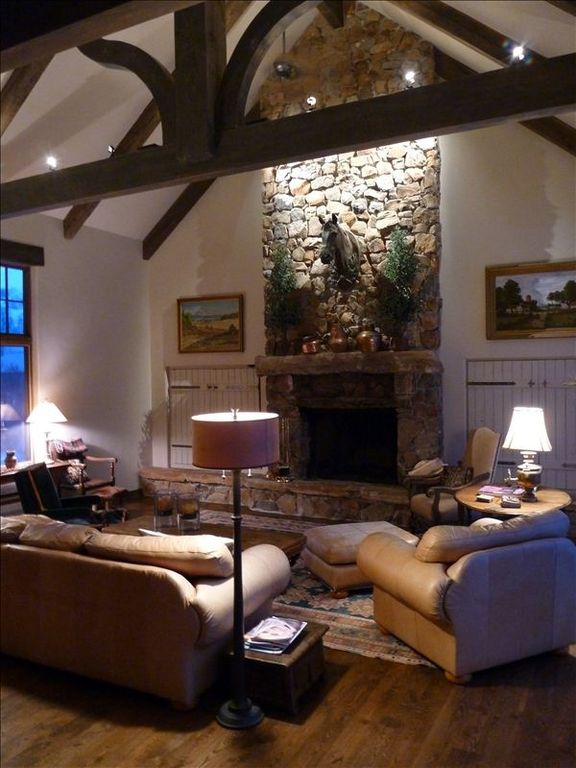 family room.with beemed ceiling,and large stone woodburning fireplace