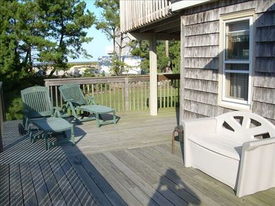 large, outside, wrap-around deck with picnic table area enclosed in back