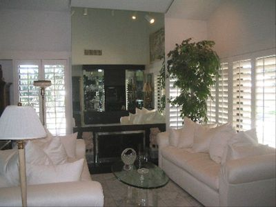 corner of living room w/ fireplace, Kreiss sofas & plantation shutters to lawns