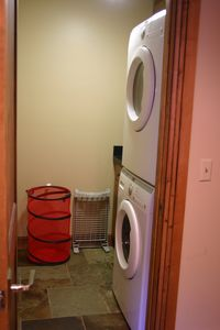 The laundry room, with full size, front-loading washer and dryer