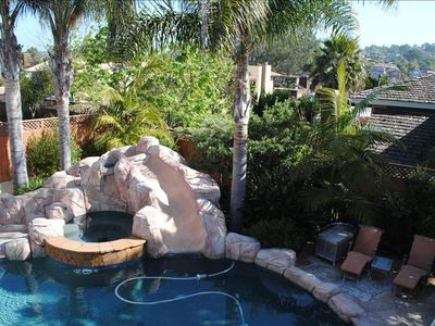 Pool with jacuzzi, slide, waterfall and surrounding furnished patio.