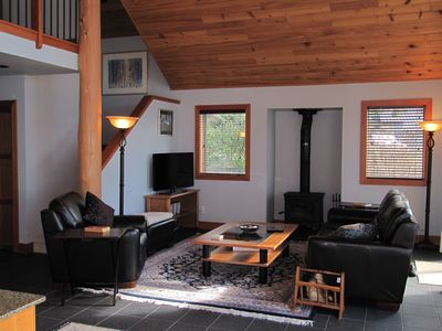 Comfortable living room with large television, wifi, and wood burning stove.