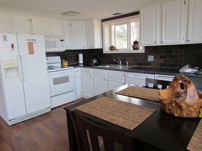 Clean Kitchen with stone backsplash, microwave, oven and full fridge