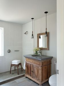 Downstairs bathroom with walk-in shower, elegant vanity and concrete countertop.
