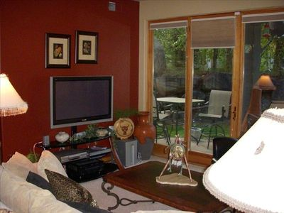 Lovely living area with entertainment center and access to patio.