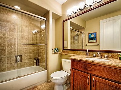 Spacious second bathroom with granite and tile.