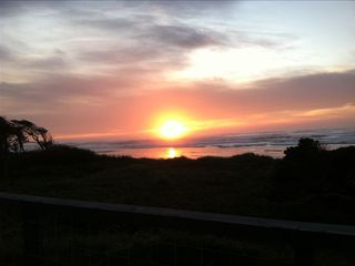 Yachats house photo - Relaxing on the top deck at sunset. This is a common scene at our place