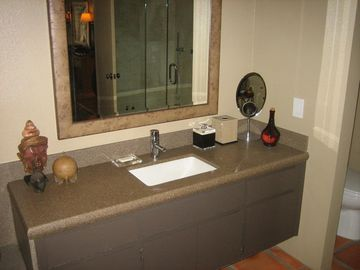 Vanity in bathroom with stone countertop and undermount sink