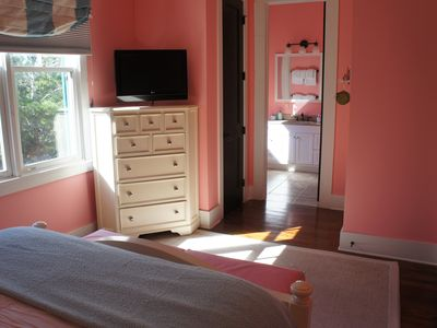 Pretty in pink room with bath with dual shower heads.