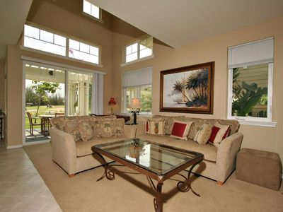 Living room with tile floors, comfortable furniture and entertainment center.