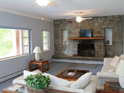 Comfortable living room, with large fireplace, satellite tv, and lots of light.