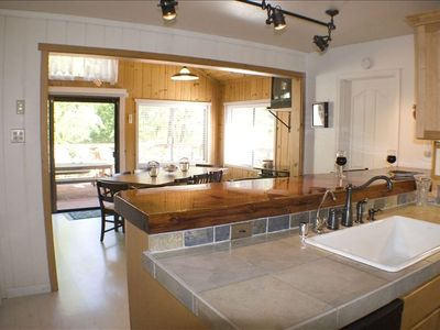 Knotty pine family/dining room with redwood tree bar overlooks the river